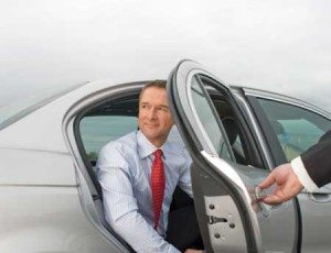 Chauffeur Opening Silver Car Door for Business Executive
